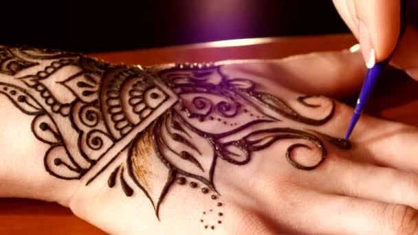 Zenske rukou se zdobí henna tetování, mehendi na černém pozadí