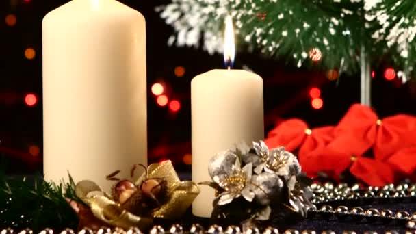Due grandi candele bianche con decorazioni natalizie come arco rosso, palle e albero sul nero, bokeh, luce, ghirlanda, cam si muove verso lalto