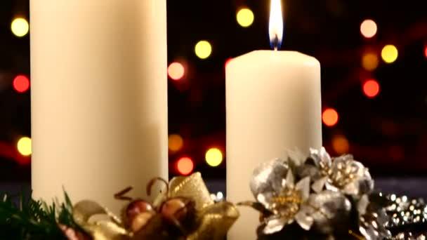 Dvě velké bílé svíčky s vánoční ozdoby jako červenou mašli, kuličky a strom na černou, bokeh, světlo, věnec, kamera se pohybuje nahoru, zblízka