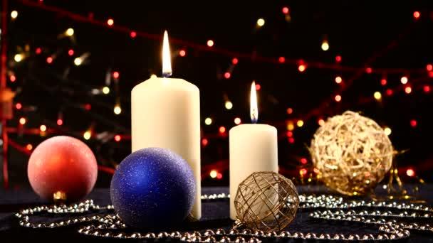 Due grandi candele bianche con palle di Natale sul nero, bokeh, luce, ghirlanda