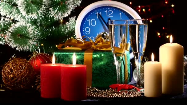 Naléval šampaňské na nový rok na nástěnné hodiny, svíčky, dárky a vánoční stromek, bokeh, věnec, na černém pozadí