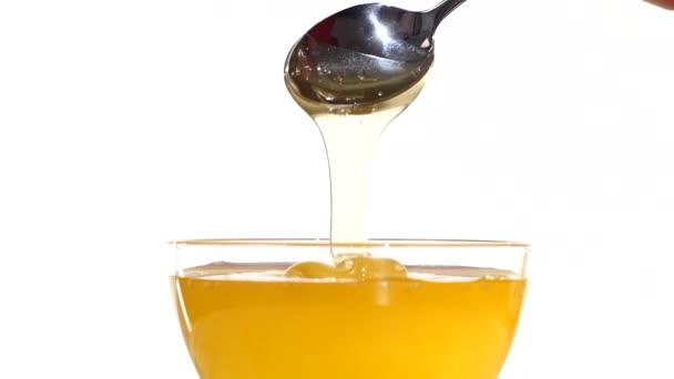 Ruka s med z nádoby pomocí kovové lžíce, na bílé, Zpomalený pohyb