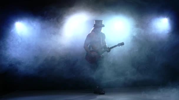 Streifen Mann Bass Gitarre spielen im Studio, Zeitlupe, Rauchen