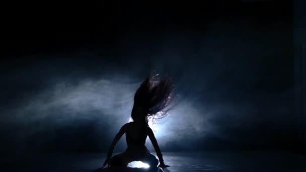 Lány hosszú fekete haj, fekete öltöny. Lassú mozgás, füst