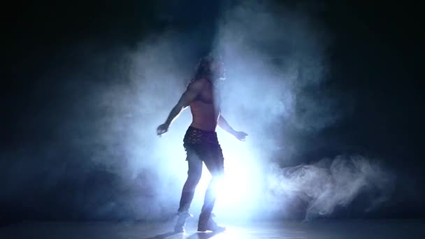 young naked man silhouette of a young man dancer. Slow motion, smoke