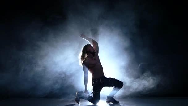 Night-club táncos, izmok ember sziluettje egy fiatal férfi táncos a padlón. Lassú mozgás, füst