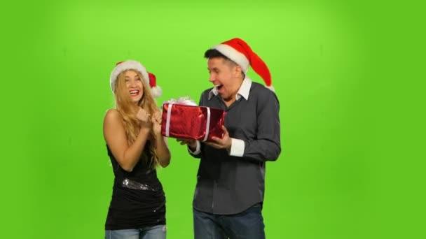 mladý muž dává vánoční dárek k jeho překvapení přítelkyni. zelená obrazovka