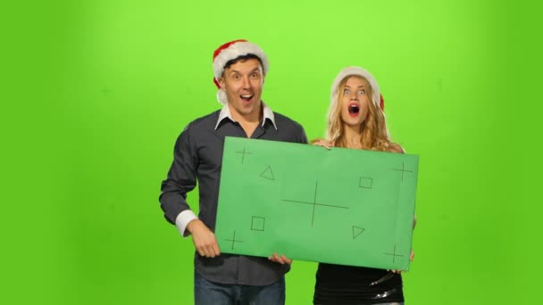 man and woman: new years eve. green screen, blank sign