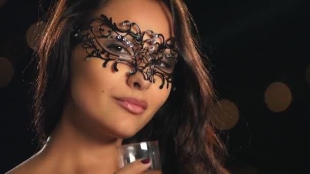 Krásná žena v karnevalové masce na černém pozadí. Zblízka, bokeh
