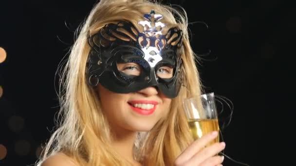 Blonde Frau mit venezianischer Maske und einem Glas Champagner auf schwarzem Bokeh