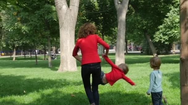 glückliche Familie: Mutter dreht Drehkreisel mit ihren kleinen Töchtern. Zeitlupe