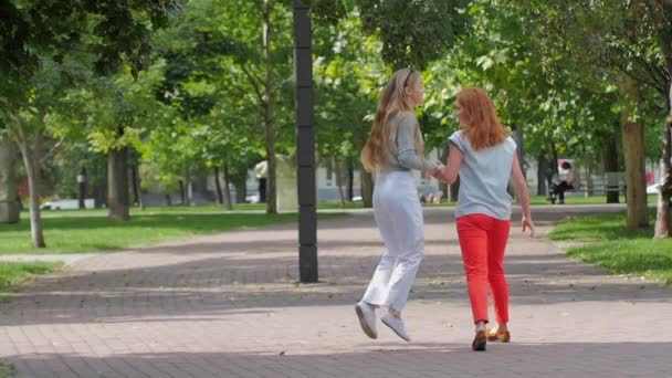 Teenage girls having fun and jumping in spring park. slow motion