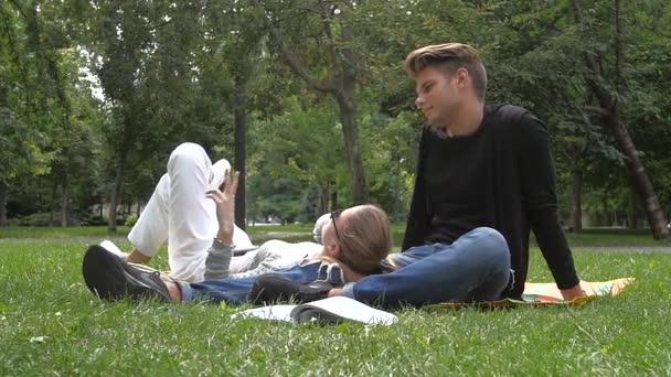 Šťastný úsměv pár v lásce studentů relaxační na zelené trávě. Zpomalený pohyb