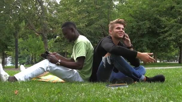 Mladí studenti čtení knih na školní park. Zpomalený pohyb