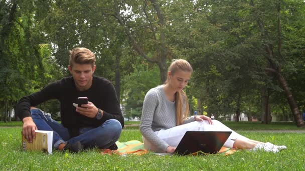 Couple watching and sharing videos in a tablet in a green field. slow motion