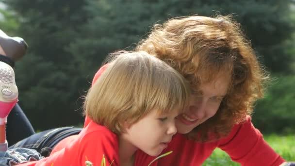 pěkná matka a dcera šeptání drby na trávě. Zblízka