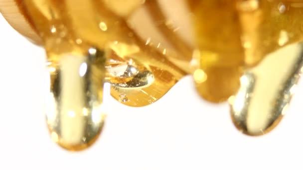 Med z dřevěnou lžící, jedna kapka, na bílém pozadí