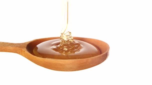 Med z dřevěné honey naběračka na bílém pozadí