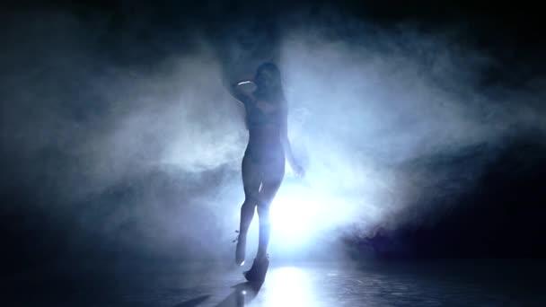 striptease woman dancer posing on studio background. Slow motion, smoke