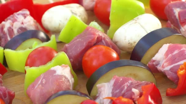 Assorted meat from chicken, pork and various vegetables for barbecue on cutting board, rotation, close up, top view