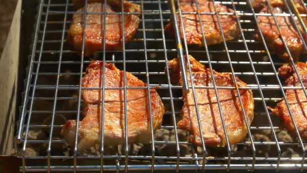Grilled pork steaks over flames and coals, on the brazier, cam moves to the right, close up