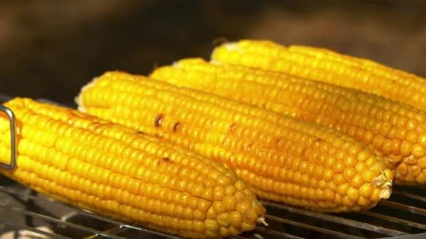 Zdravě vegetariánský gril s zralou zlatou kukuřicí na uhlí, otočte ho pomocí gril kleště