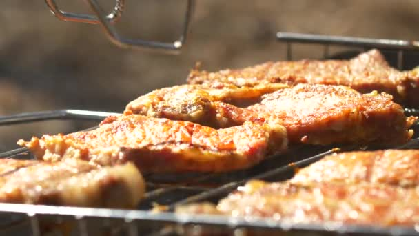 Grilled steaks over flames and coals, on the brazier, turn slices, close up