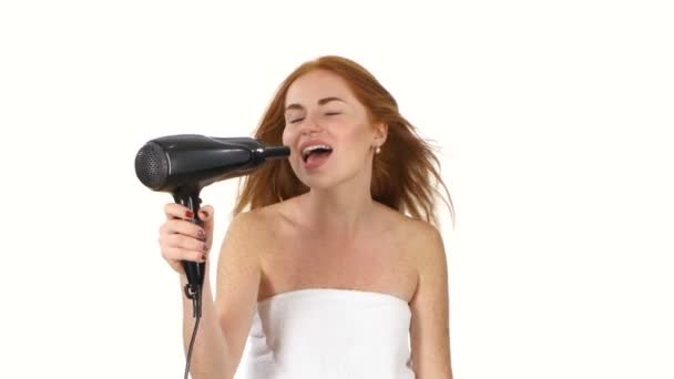 Smiling young Redhead girl singing while blow-dry, bathroom