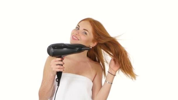 Redhead woman in bathroom drying hair with blow dryer, bathroom