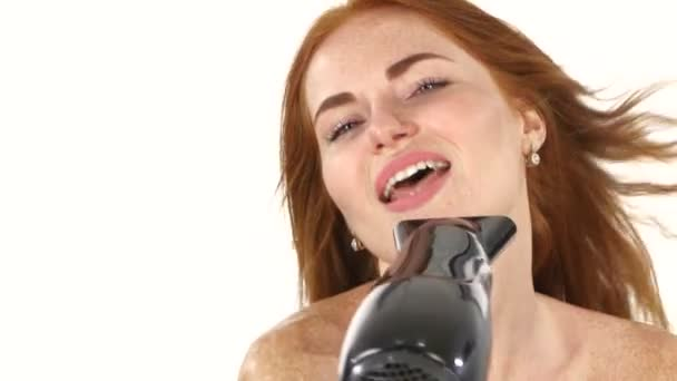 Smiling young Redhead girl singing while blow-dry. Close up,bathroom