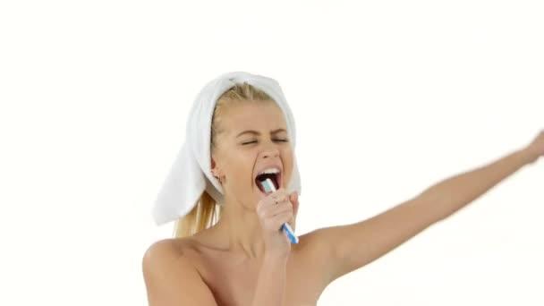 Happy pretty woman singing to tooth brush, bathroom
