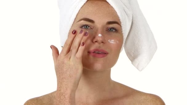 Beautiful young  woman applying  cream on face. Close up, bathroom