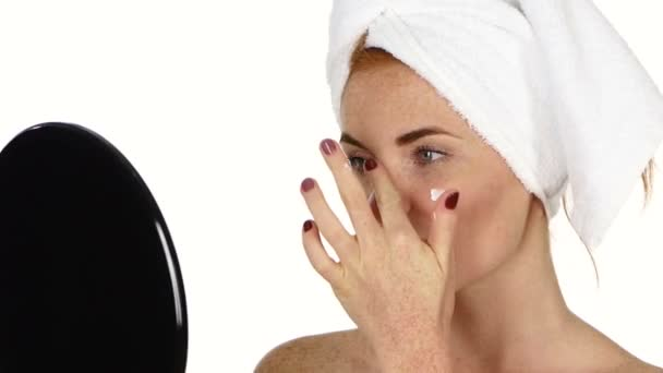 young woman applying face cream. Close up, bathroom