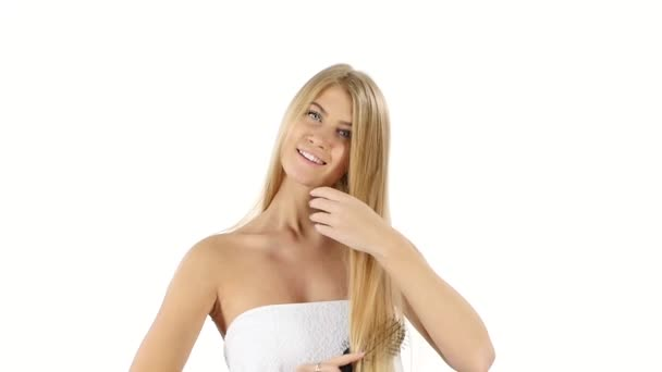 woman with long straight blond, Brushing Her  Hair, slow motion. Close up, bathroom