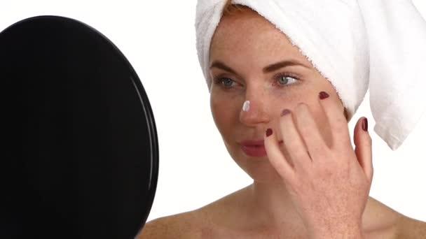 Žena, použitím krém na obličej. Zblízka. Zpomalený pohyb