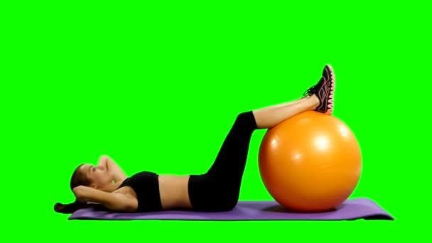 žena v tělocvičně oblečení cvičení pilates míč, zelená obrazovka