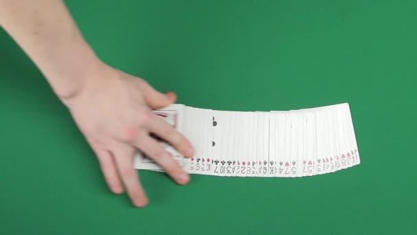Spielkarten, die von Magier in Zeitlupe auf einer grünen Oberfläche verteilt werden
