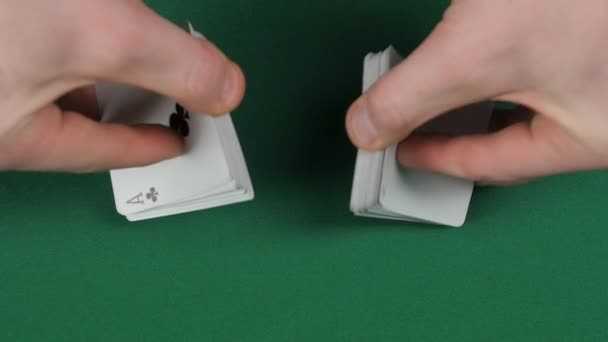 Playing cards being shuffle, on a green surface by magician, close up, slow motion