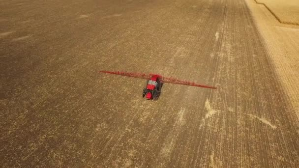 Tractor sprays which protect against pests at a farmers field corn, aerial shot