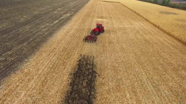 Vörös traktor előkészítése földet vetés. légi lövés, szántóföldi kukorica