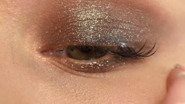 Makeup artist glues eyelashes. Beautiful woman face. Close up