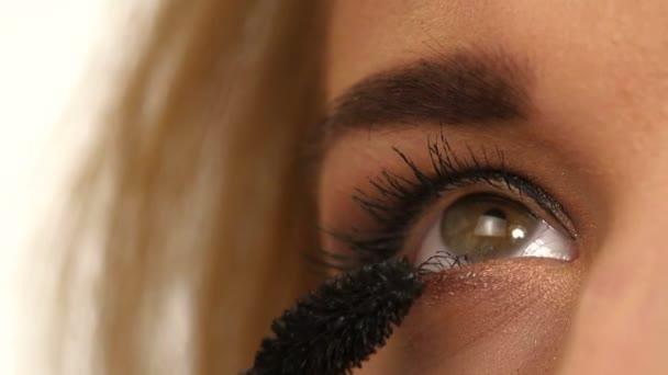 Woman applying mascara on her long eyelashes. close up