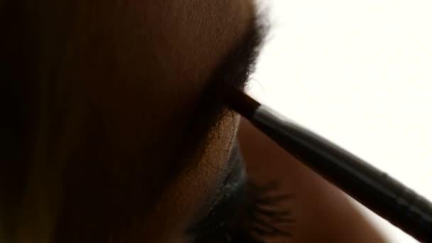 Beautiful woman draw beauty shape of eyebrows using cosmetic brush, Close up