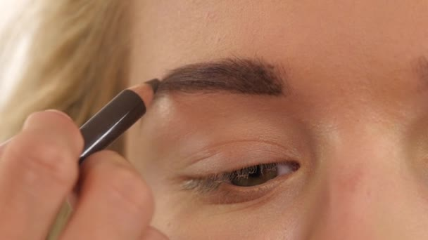 young girl draw beauty shape of eyebrows using cosmetic brush. Close up. Slow motion