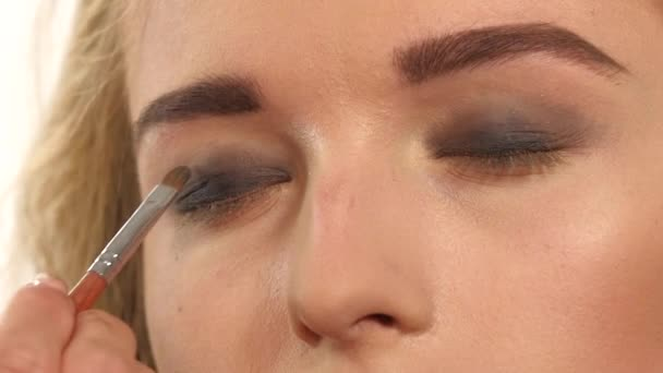 Make-up artist applying bright base color eyeshadow on models eye and holding a shell with eyeshadow. Slow motion