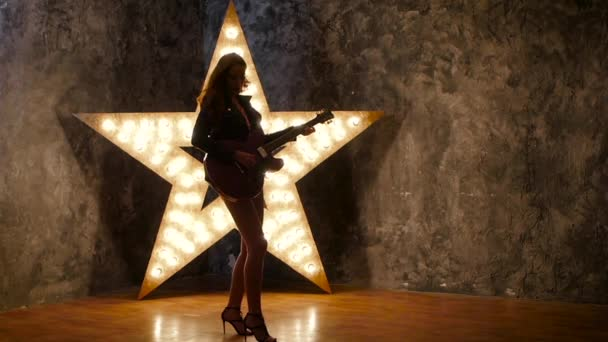 Female punk rock guitarist, dances. shining star in the background. slow motion, silhouette