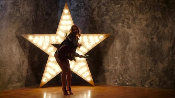 sexy rock girl dancing with electric guitar, shining star in the background. slow motion, silhouette