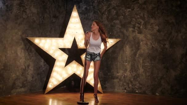 szexi lány, aki egy Mike és énekelte a jazz. ragyogó csillag a háttérben, lassított