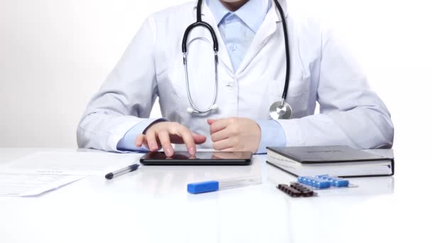Doctor searching something on the tablet and writes something, wearing stethoscope, white
