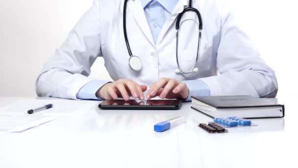 Doctor typing something on the tablet, wearing stethoscope, white